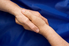 Agitação da mão de encontro a um fundo azul Fotografia de Stock