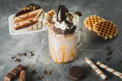 Agitação de chocolate com leite, molho de gotejamento, creme, cookies e bolo imagem de stock