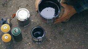 A agitação do artista uma pintura preta em uma lata e em derramá-la a outra pode filme