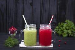 Agitação do batido do suco da caneca de dois vidros da salsa verde, do aneto, dos brócolis, do abacate e do arando vermelho no fu Imagem de Stock Royalty Free