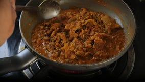 Agitação Fried Pork Curry em uma fritura filme