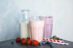 Agitações e ingredientes de leite deliciosas na tabela fotos de stock