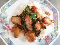 Agitaci?n Fried Spicy Crispy Pork con albahaca tailandesa fotografía de archivo