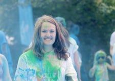 Agitando, mujer hermosa joven sonriente cubierta con polvo del color Imágenes de archivo libres de regalías