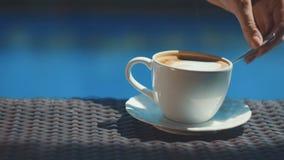 Agitando o copo do cappuccino com colher e tomada dela da tabela de vime filme
