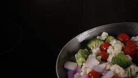 Agitando vegetais em uma frigideira vídeos de arquivo