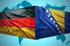 Agitar banderas bosnios y alemanas Foto de archivo libre de regalías