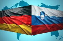 Agitar banderas eslovenas y alemanas Imagen de archivo