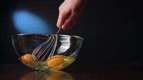 Agitar eggs em uma bacia de vidro com uma suiça fotos de stock