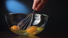 Agitar eggs em uma bacia de vidro com uma suiça foto de stock
