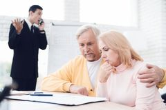 An agitated couple of old people at a reception with a realtor. The realtor is excitedly discussing something on phone. An agitated couple of old people at a Royalty Free Stock Photo