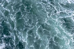 Agitated ocean waters from big ship wake. Water white and blue agitated, big ship boat wake in the deep sea stock photos