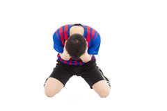 Agitated soccer player kneel down and  cover his face to cry. In studio Royalty Free Stock Image