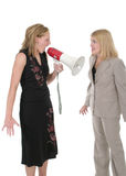 Agitated Two Business Women Team 4. Extreme two person business team with one worker shouting commands through a megaphone Royalty Free Stock Photo