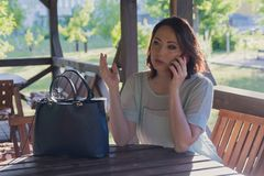 Agitated woman is talking on a smartphone in the gazebo of a street cafe. People stock photos