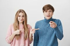 Agitated young couple dressed in knitted sweaters gesturing actively, girl blaming boy, male looking worried. Body. Portrait of agitated young couple dressed in Stock Image
