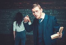 Agitated young professor passionately explaining mathematic formula. Handsome teacher holding a book while giving a. Lecture at university royalty free stock images
