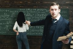Agitated young professor pointing at green board with a lot of writing done by female student in white jumper and blue. Jeans stock photo