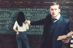 Agitated young professor pointing at green board with a lot of writing done by female student in white jumper and blue. Jeans royalty free stock photography
