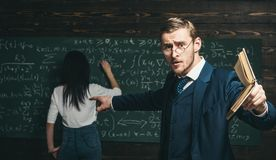 Agitated young professor with stylish mustache and beard pointing book at students in classroom while showing formula. Brunette girl is writing on board royalty free stock images