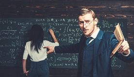 Agitated young professor with stylish mustache and beard pointing book at students in classroom while showing formula royalty free stock photos