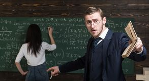 Agitated young professor teaching math at college. Brunette female student solving equation on green board.  royalty free stock image