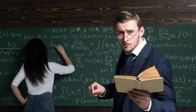 Agitated young teacher with anxious look standing in the classroom with book and chalk in his hands. Young student. Solving task on green board stock photography