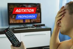 Troubled man watching news about civil riots,. Agitation and propaganda in the modern television. Misinformation citizen. Remote control in the hand of the guy Royalty Free Stock Photos