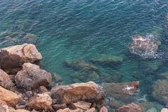 Agite el agua del mar cerca de la foto de la piedra de la roca Foto de archivo libre de regalías