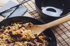 Agite macarronetes da fritada em uma bandeja preta com concha de bambu, e com a bacia brilhante preta Fotografia de Stock Royalty Free