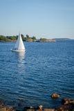 Żaglówka i skalista linia brzegowa w ładnym czystym morzu Obrazy Royalty Free