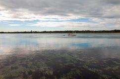 Żaglówka pływa statkiem z furled żaglami na Australijskim jeziorze Obraz Stock