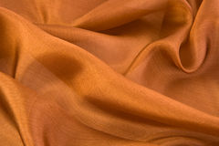 Aglint brown silk. Folds on brown aglint silk close-up Royalty Free Stock Photo