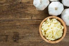 Aglio bianco schiacciato in ciotola di legno con i chiodi di garofano di aglio sulla tavola di legno Fotografie Stock Libere da Diritti
