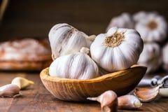 aglio Chiodi di garofano di aglio e lampadina dell'aglio in ciotola di legno d'annata Fotografie Stock