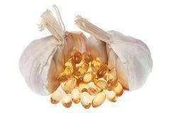 Aglio con le capsule molli dell'olio isolate su fondo bianco Fotografia Stock Libera da Diritti