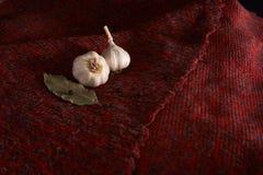 Aglio, foglia di alloro, pepe nero su un tessuto rosso Priorità bassa dell'alimento garlics aglio affettato, chiodo di garofano d fotografia stock libera da diritti