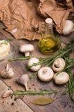 Aglio, funghi, burro, rosmarini e olio d'oliva su un fondo di legno Una carta sgualcita e foglie della baia sullo scrittorio Fotografia Stock