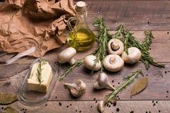 Aglio, funghi, burro, rosmarini e olio d'oliva su un fondo di legno Una carta sgualcita e foglie della baia sullo scrittorio Fotografia Stock Libera da Diritti