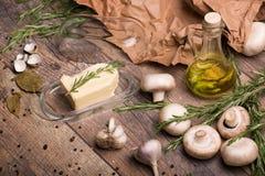 Aglio, funghi, burro, rosmarini e olio d'oliva su un fondo di legno Una carta sgualcita e foglie della baia sullo scrittorio Immagini Stock