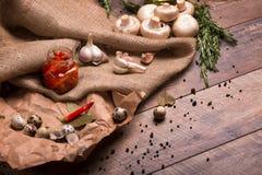 Aglio piccante, una banca trasparente dei peperoni caldi, uova di quaglia e rosmarini su un fondo di carta e di legno sgualcito Fotografia Stock