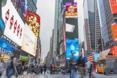 Aglomerado do turista que anda no Times Square com diodo emissor de luz assina Foto de Stock