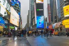 Aglomerado do turista que anda no Times Square com diodo emissor de luz assina Fotografia de Stock