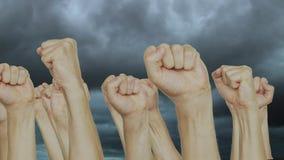 Aglomere os povos que aumentam o punho acima apertado acima no fundo sombrio do céu vídeos de arquivo