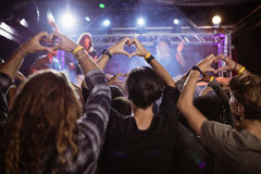 Aglomere-se fazendo a forma do coração com mãos durante o desempenho Fotos de Stock Royalty Free