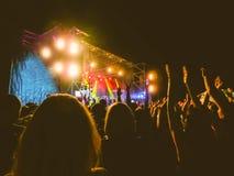 Aglomere-se levantando suas mãos e apreciando o grande partido ou concerto do festival Imagem de Stock