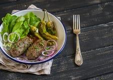 Agnelez le chiche-kebab, les poivrons rôtis épicés et la salade verte fraîche du plat sur une surface en bois foncée Photo libre de droits