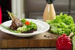 Agnelez les nervures juteuses délicieuses d'agneau de nervures sur des légumes de gril avec le souce Photos libres de droits