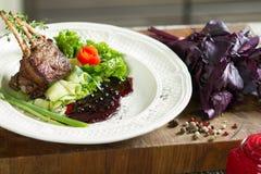 Agnelez les nervures juteuses délicieuses d'agneau de nervures sur des légumes de gril avec le souce Photo stock