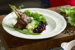 Agnelez les nervures juteuses délicieuses d'agneau de nervures sur des légumes de gril avec le souce Image stock
